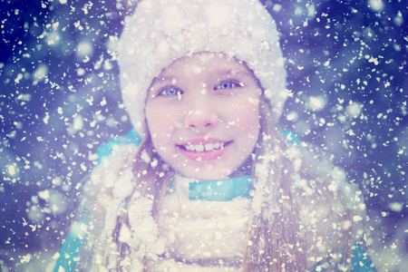A beautiful portrait of a cute blond girl kid in snowflakes, happily smiling.
