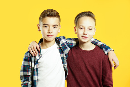 Child boys are best friends hugging and looking at the camera over yellow background. Two brothers together 免版税图像
