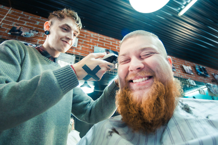 A redhead bearded man sitting in barber shop and laughing.