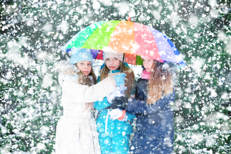 Three little girls during snowfall under umbrella in a forest.