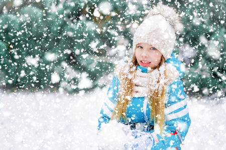 A pretty girl kid in heavy snowfall making snowballs facing camera.