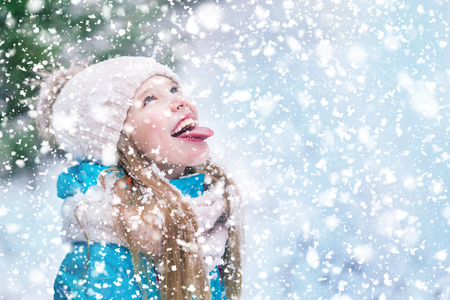 Catching snowflakes on tongue of a cute child over snowy blue background. 免版税图像 - 116017959