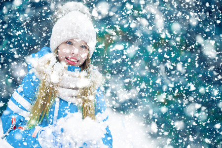 A beautiful girl kid smiling with a snowball in hand on a snow blue background. 免版税图像