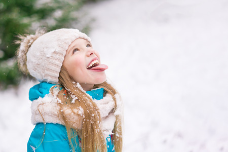 A cute blond little girl puts her tongue out trying to catch snowflakes. 免版税图像 - 116017963