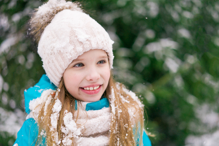 A pretty girl child in winter hat with a kind smile looking at someone aside in park.