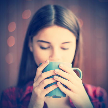 A closeup of calmful girl and her tea in a peaceful atmosphere.