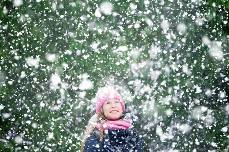A snowing background with a happy kid on it in a forest. 免版税图像