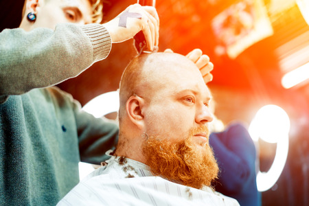 A male hairstylist is making head of bearded man bald done.