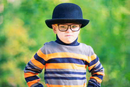 Angry liittle boy wearing a hat and glasses outdoors