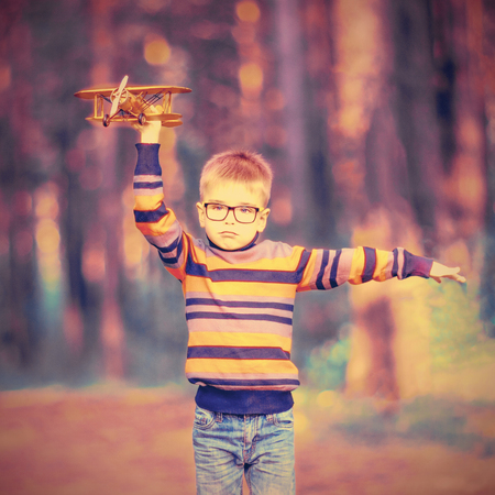 Funny little boy wearing glasses playing with toy airplane outdoors. Dreams of traveling