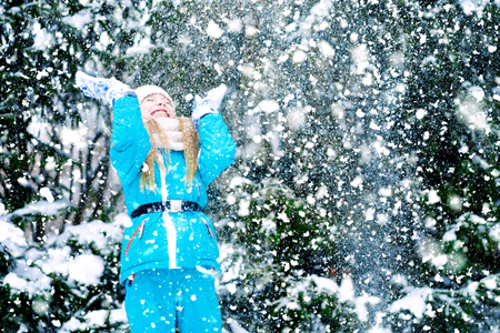 A happy girl kid is playing during snowfall weather in a winter forest.