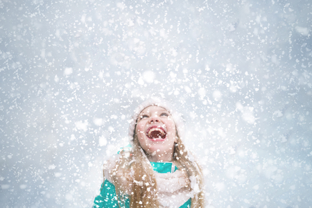 A blond girl child happily opens mouth to catch snowflakes during snowfall. 免版税图像 - 116018123
