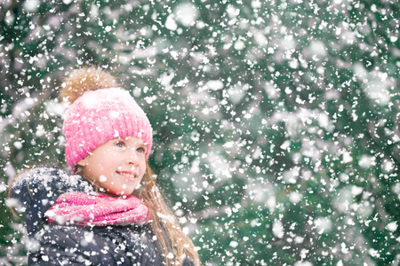 Beautiful girl child in pink hat is happy seeing falling snowflakes in winter forest.