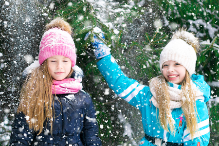 Two cute little girl friends have fun playing in a snowy forest.