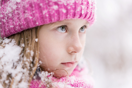 A closeup of a child in pink hat and snow on hair and serious look. 免版税图像