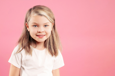 Happy smiling little girl over pink background with copy space