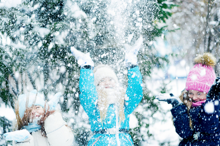Happy little girls screwed up their eyes throwing up snow in a winter forest. 免版税图像