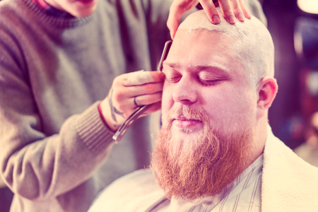 A redhead bearded man is pleased to make grooming of his hairstyle in this barbershop.