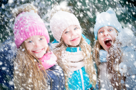 A portrait of cute little girls with funny faces and falling snowflakes. 免版税图像 - 116018132