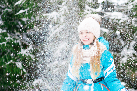 Happy cute little girl in white hat throws up the snow on a forest walk.