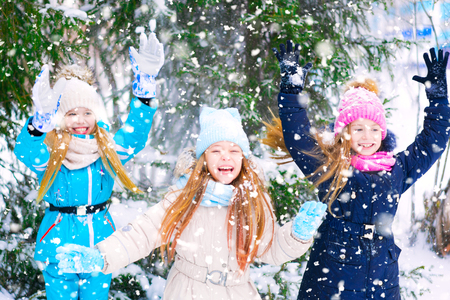 Three little girls happily raising their hands laughing in a winter forest during snowfall.