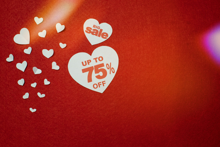 Symbol of heart for big sale with 75 percent next to other smaller white hearts on the red background. Discount promotion