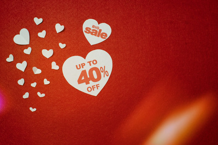 Symbol of heart for big sale with 40 percent next to other smaller white hearts on the red background. Discount promotion