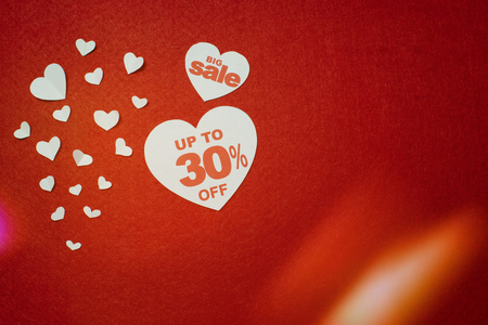 Symbol of heart for big sale with 30 percent next to other smaller white hearts on the red background. Discount promotion