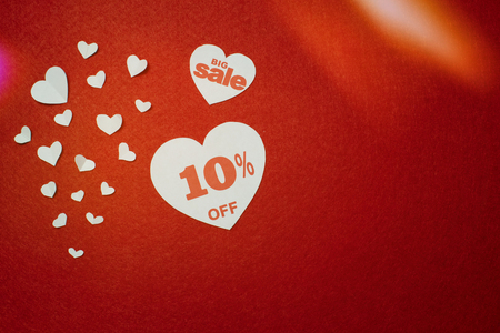 Romantic symbol for sale in the form of a heart with ten percent next to other smaller white hearts on the red background. Discount promotion