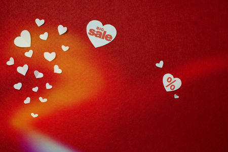 Big sale written on one of white hearts on a red background near other smaller hearts. Valentines day