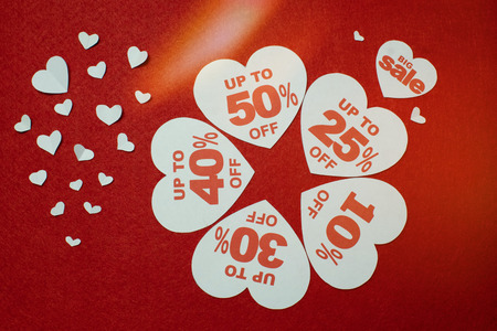 Symbols of hearts laid in the form of star for sale. Five white hearts in which the numbers are written in the centre over red background Standard-Bild