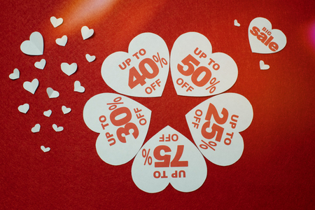 White hearts shaped sales promotion tag against a red background. Sales and discounts inside hearts