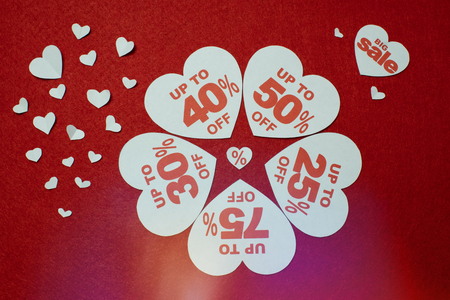 Discount promotion sale. Five big white hearts with per cent numbers surrounded by other small hearts over the red background.