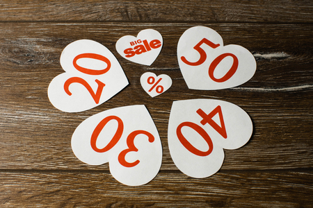 Discount promotion sale. Four big white hearts with per cent numbers and smaller one for big sale over wooden background. Close up