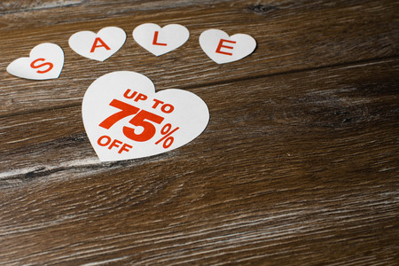 White paper hearts with discount up to 75 percent and smaller hearts with letters for word sale isolated on brown wooden background. Standard-Bild