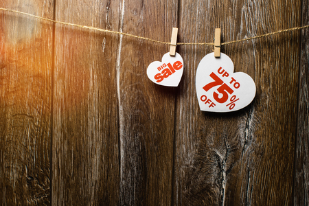 Hearts and discounts with romantic pattern on wooden background. Big sale on one heart and seventy-five percent on another hanging on rope by clothespins Standard-Bild