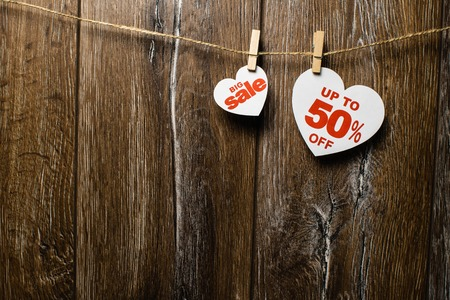 Hearts and discounts with romantic pattern on wooden background. Big sale on one heart and fifty percent on another hanging on rope by clothespins Standard-Bild