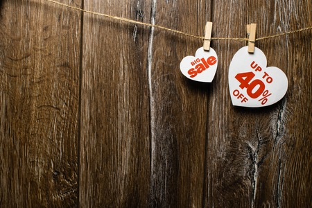Hearts and discounts with romantic pattern on wooden background. Big sale on one heart and forty percent on another hanging on rope by clothespins