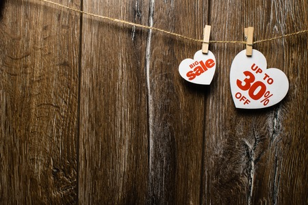 Hearts and discounts with romantic pattern on wooden background. Big sale on one heart and thirty percent on another hanging on rope by clothespins