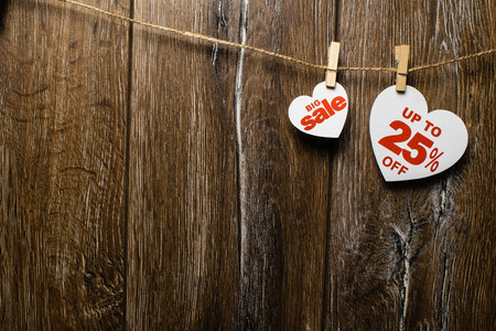 Two white hearts and discounts with romantic pattern on wooden background. Big sale in one heart and twenty-five percent on another hanging on rope by clothespins