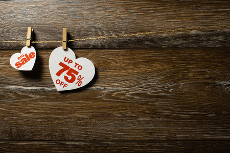 Big sale on hearts hanging on rope with clothespins over the wooden background. Seventy-five percent discount promotion written on white heart Standard-Bild
