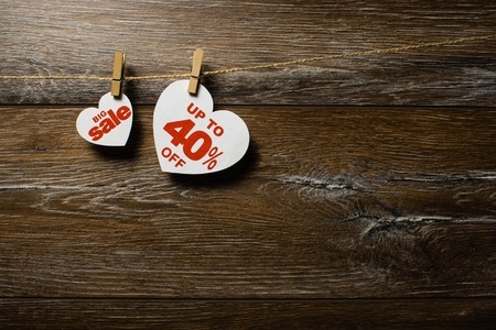 Big sale on hearts hanging on rope with clothespins over the wooden background. Forty percent discount promotion written on white heart