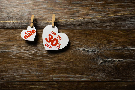 Big sale on hearts hanging on rope with clothespins over the wooden background. Thirty percent discount promotion written on white heart