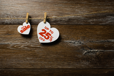 Big sale on hearts hanging on rope with clothespins over the wooden background. up to 25 off discount written on white heart