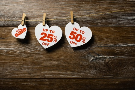 Three white hearts with discounts hang on the clothespins on the rope isolated on brown wooden background. Big sale up to 25 and 50 percent Standard-Bild