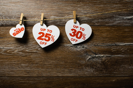 Three white hearts with discounts hang on the clothespins on the rope on brown wooden background. Big sale up to 25 and 30 percent