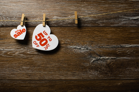 White hearts and discounts with romantic pattern on wooden background. Hearts of fifty percent hanging on rope by clothespins