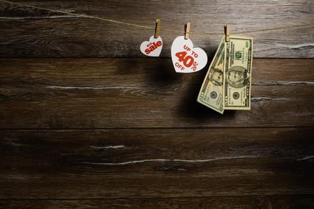 Cash of dollars hanging on a string near the hearts with 40 percent for big sale on wooden background. Sale on Valentines. Stock Photo