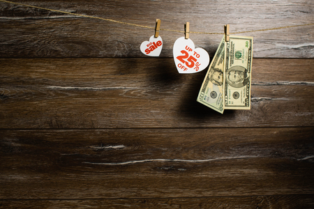 Big sale to 25 percent written on white heart and hang on clothesline with two banknotes of dollars on wooden background