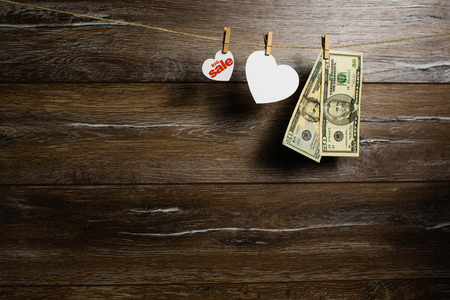 American dollars in two banknotes and hearts for big sale hanging with clothespins on wooden background. Holiday sale
